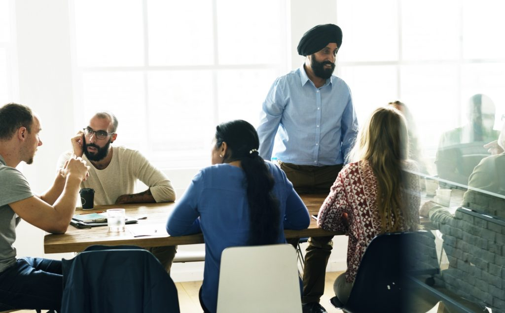 south asian man leading a meeting