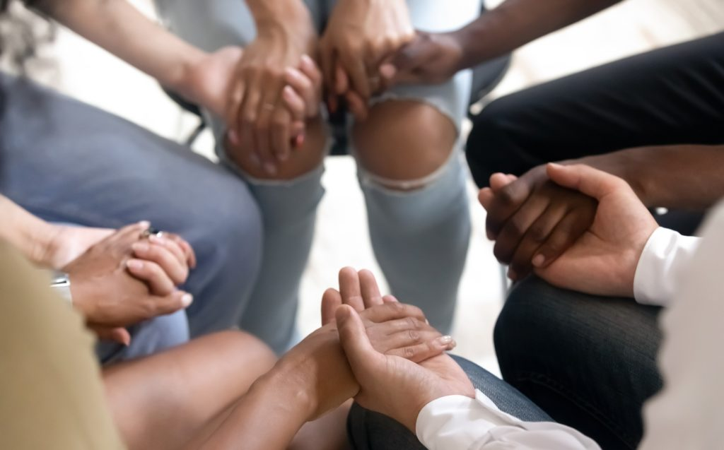 diverse group of people sitting in a circle holding hands at group therapy